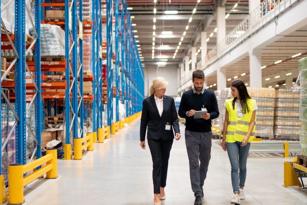 three employees walking through a warehouse discussing 3pl ecommerce fulfillment