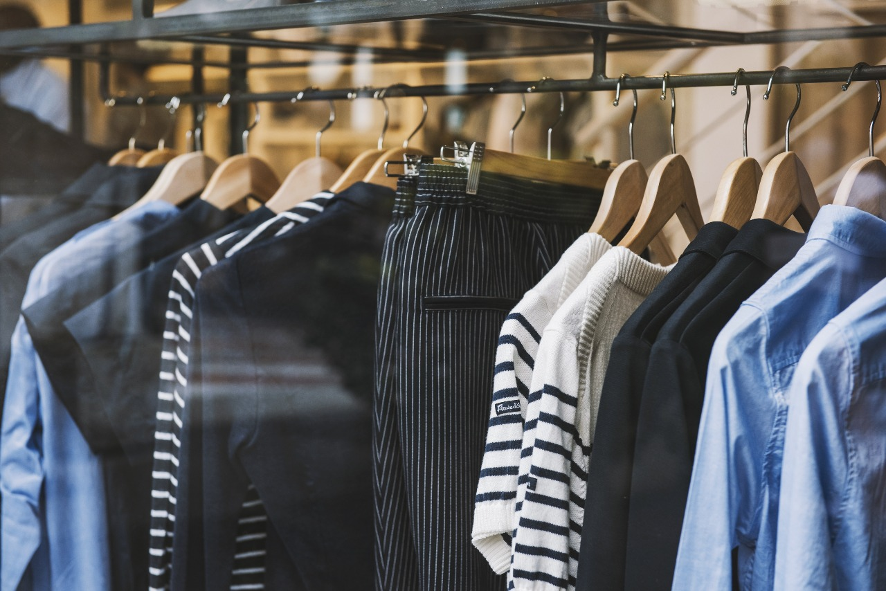 shirts and pants on hangers hanging on a rack illustrating ecommerce fulfillment services
