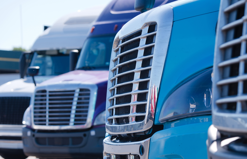close up of the front of big rig trucks that are used for ground freight shipping companies