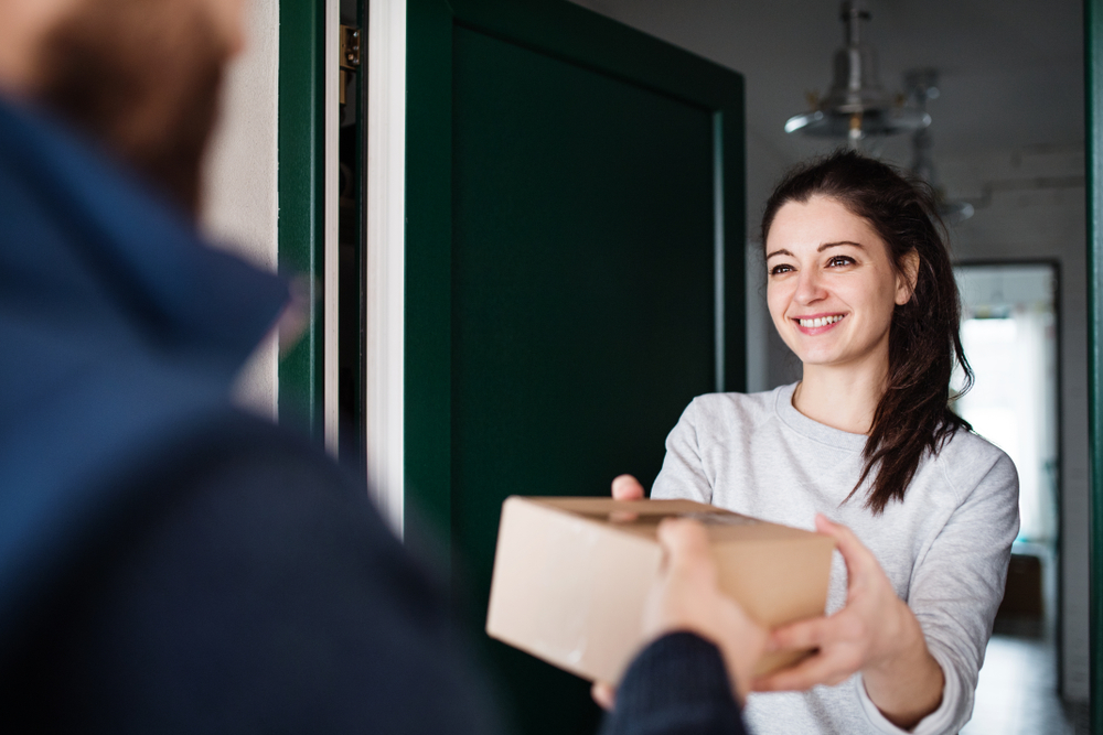 lady receiving a package at home being delivered from an ecommerce fulfillment center