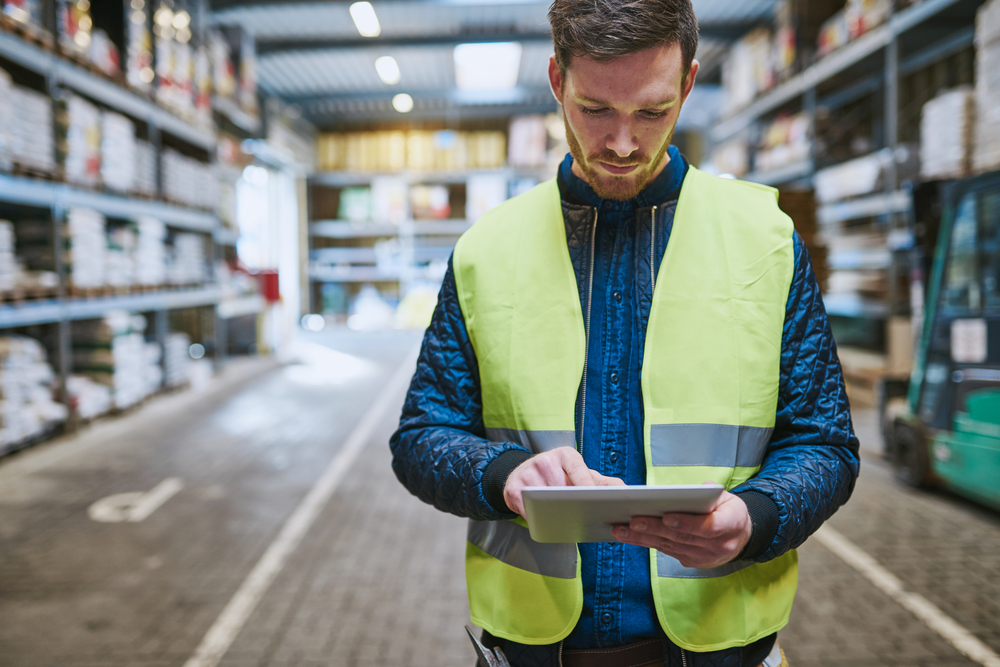 man working with management software on a tablet in a warehouse
